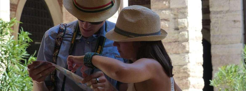 Una coppia di turisti in Cortile Mercato Vecchio consulta la mappa di Verona a Ferragosto