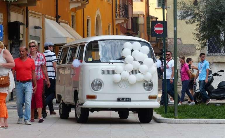 Un furgoncino Wolkswagen bianco con tanti palloncini parcheggiato a San Nicolò all'Arena di Verona in attesa degli sposi