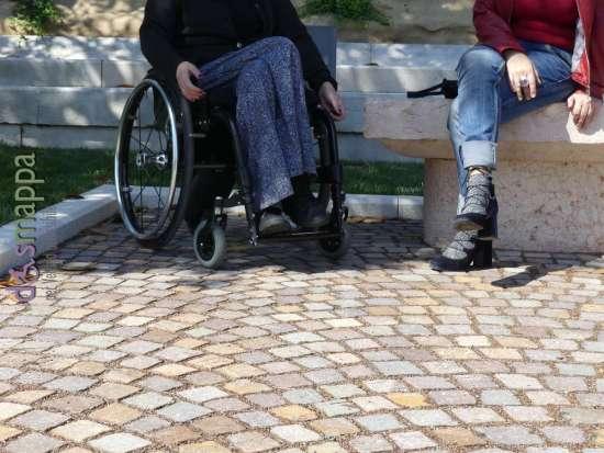Lo spazio riservato alle persone con disabilità in sedia a rotelle accanto alle panchine in Lungadige San Giorgio a Verona