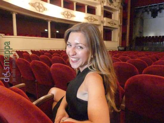 La giornaliste Alessia Bottone posa sorridente tra le poltrone  del Teatro Nuovo durante la registrazione del documentario Vorrei ma non posso