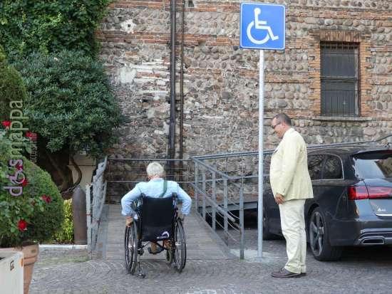 Donna disabile in sedie a rotelle sulla rampa laterale del Palazzo della Gran Guardia a Verona