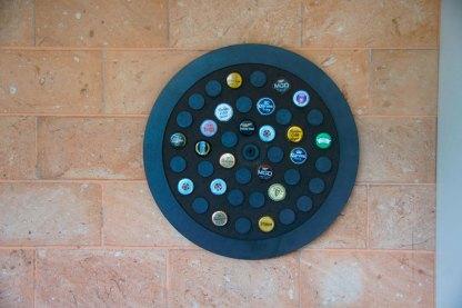 Display circular decorativo para 42 tampinhas em MDF usinado com acabamento laminado preto.