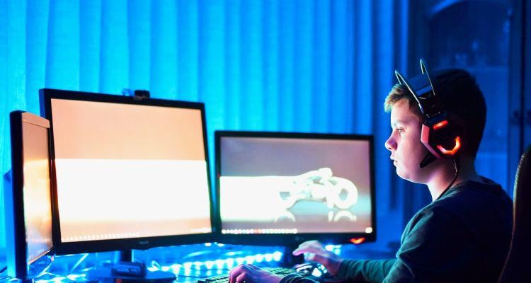 un garçon jouant devant 3 écrans PC Gamer