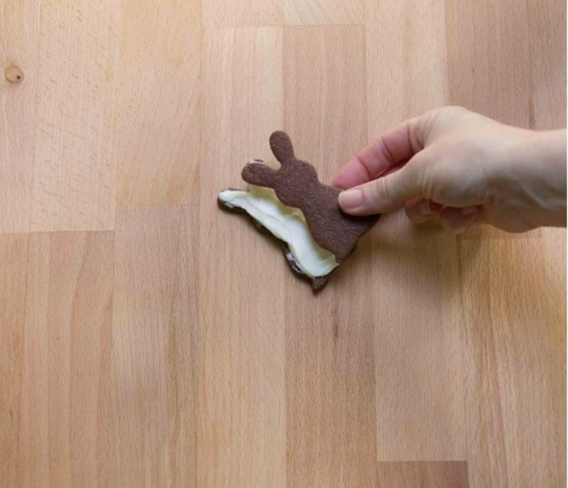 una mano che appoggia un biscotto sull'altro dopo averlo spalmato con la crema