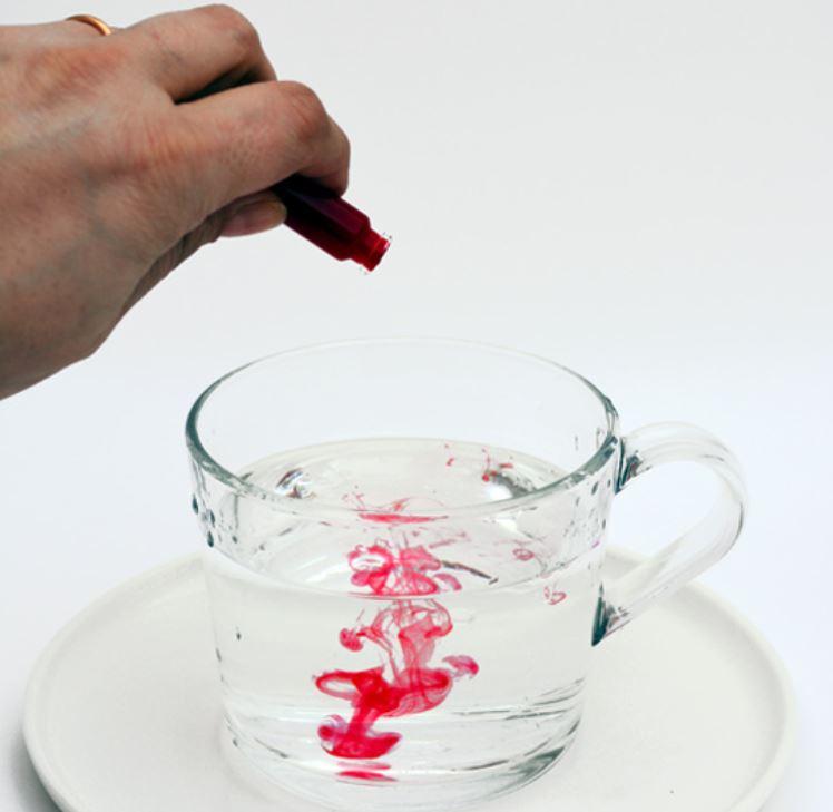 tazza con acqua a cui sono aggiunte alcune gocce di colorante rosso