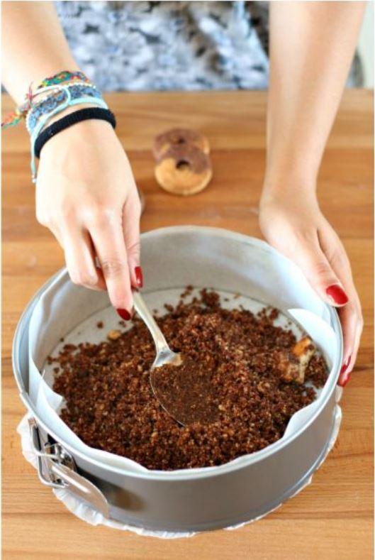 biscotti tritati a formare la base della torta in uno stampo rivestito di carta forno