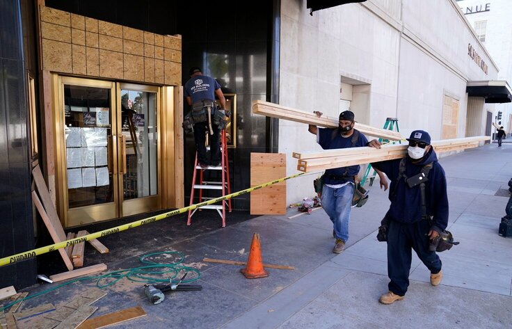 Laborers carry materials to board up windows before the upcoming election