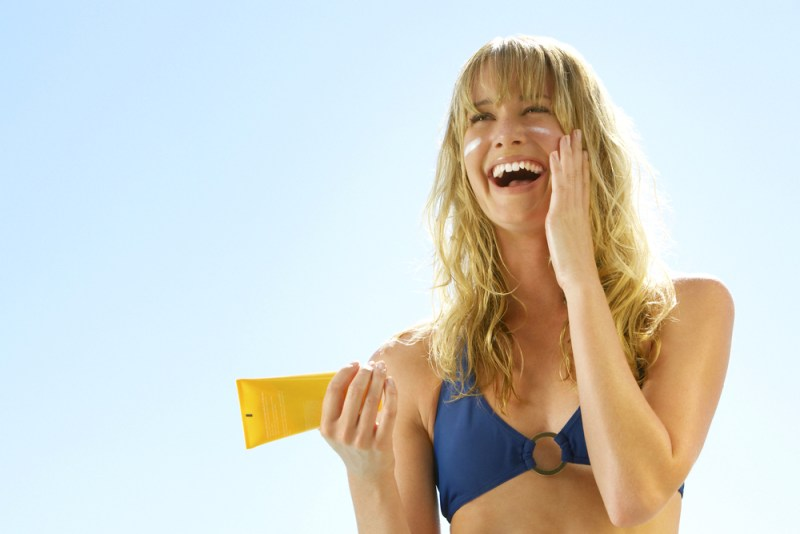Feature image for a blog post about how to protect your skin from the sun - diver putting on sunscreen -sun protection sun protection