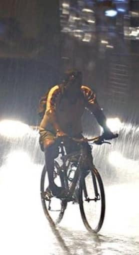 Homem andando de bicicleta na chuva