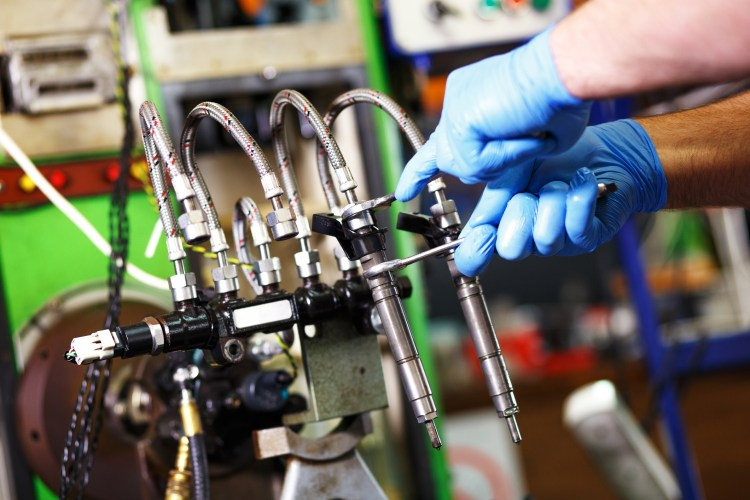 Professional mechanic testing diesel injector in his workshop.