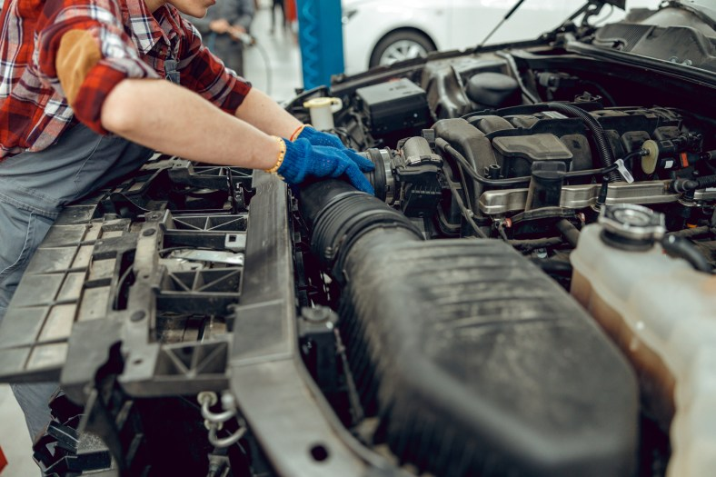 Cropped photo of a technician repairing the cooling system in the car