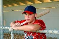 Baseball player in dugout representing baseball camps and showcases