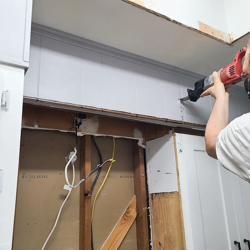 Using a reciprocating saw to remove kitchen cabinets.