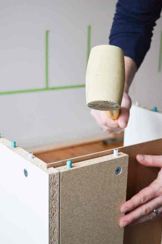 Use a rubber mallet to assemble cabinets for living room wall storage