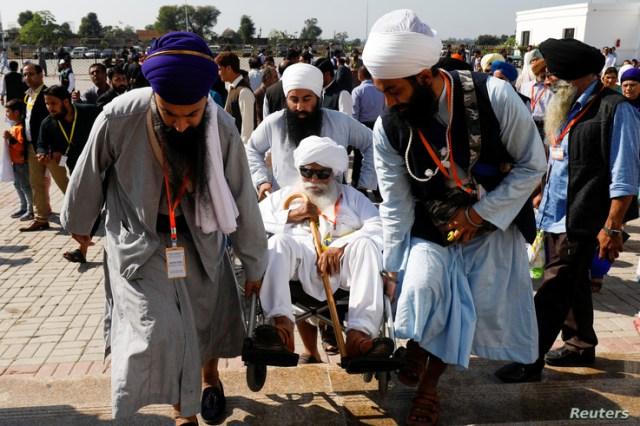 Indian Sikh pilgrims help a man on a wheelchair as they visit the Gurdwara Darbar Sahib, in Kartarpur, Pakistan, Nov. 9, 2019.