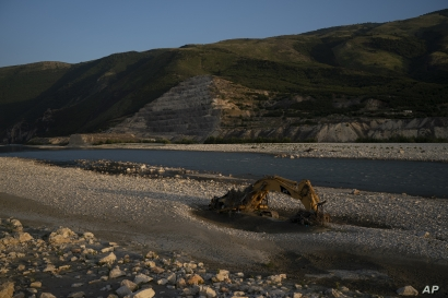 In this June 23, 2019 photo, an abandoned bulldozer sits on the banks of the Vjosa River at the construction site of the…