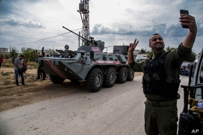 A Syrian security forces member takes a selfie by a Russian military vehicle during a patrol near the Syria-Turkey border, in northern Syria, Oct. 25, 2019.