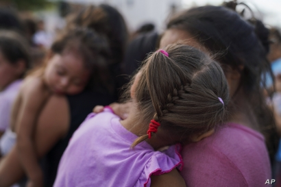 """In this Aug. 30, 2019, photo, migrants, many who were returned to Mexico under the Trump administration's """"Remain in Mexico"""" program, wait in line to get a meal in an encampment near the Gateway International Bridge in Matamoros, Mexico. The program…"""