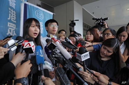 Pro-democracy activists Agnes Chow, left, and Joshua Wong speak to media outside a district court in Hong Kong, Aug. 30, 2019.