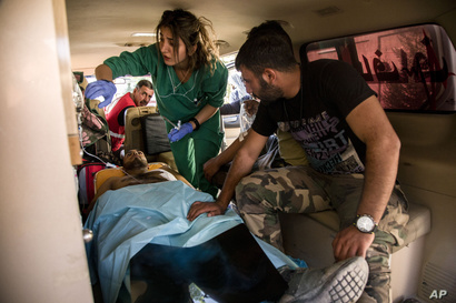 Syrian army soldiers wounded in fighting with Turkish and Turkish-backed forces are evacuated to a hospital from a frontline near the town of Tal Tamr, Syria, Nov. 9, 2019.