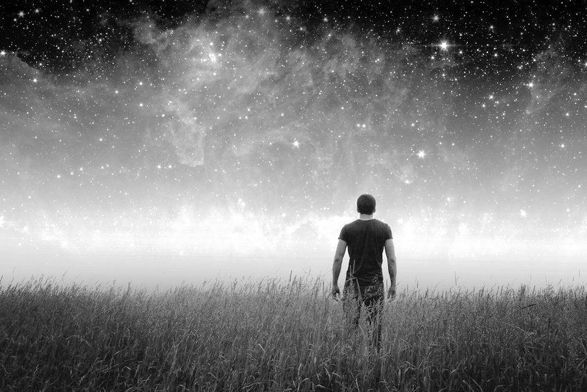 Ser humano en un campo mirando el cosmos.