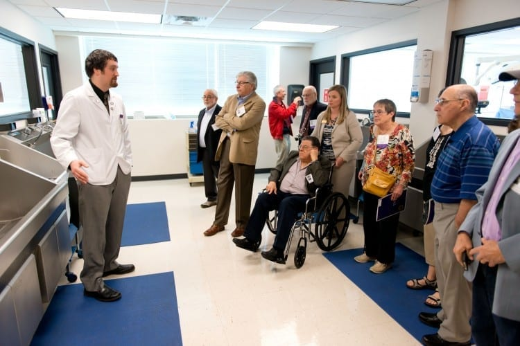 Student explains Surgery Lab to alumni tour group at 2014 Reunion