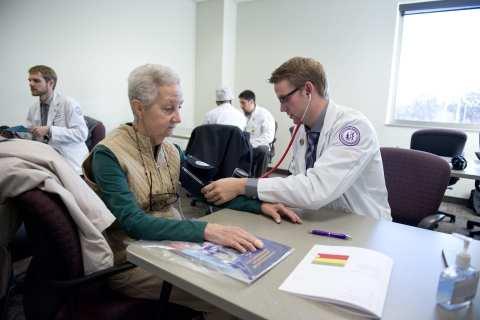 Elderly female Senior Health Fair attendee gets blood pressure screening from make student in white coat