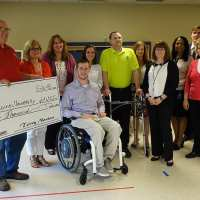 SCI CAN's Chris Norton and family present a $60,000 check to Katie Stevermer and Des Moines University representatives.