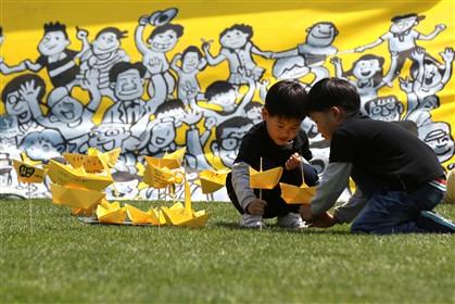 Crianças brincam com barcos de papel amarelos perto do memorial que foi erguido em Seul, na Coreia do Sul, em memória das vítimas do naufrágio do navio 'Sewol'