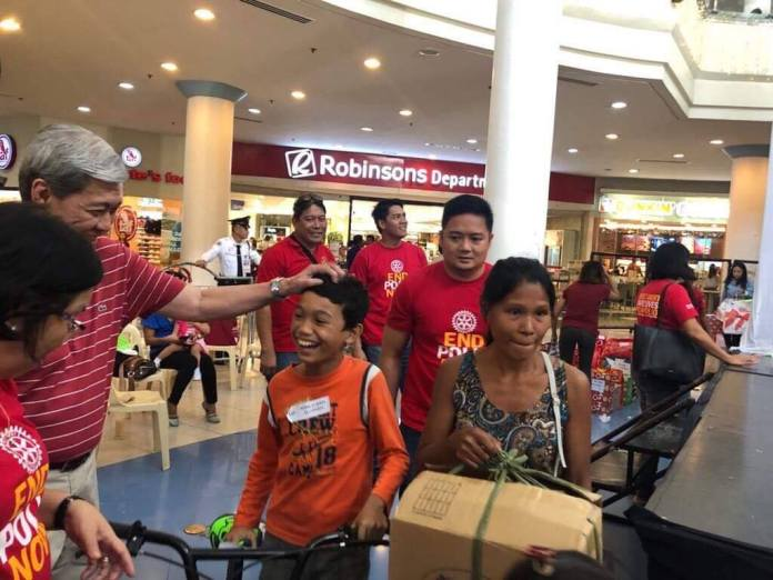 A beneficiary beams as he carries off his gift during the annual gift-giving of Rotary Club in partnership with Robinsons Malls.