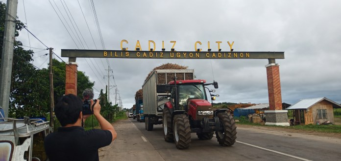 A tractor hauling canepoints passes through the welcome arch leading into Cadiz City as DNX TV unit head Banjo Hinolan shoots B roll. | Photo by Richard D. Mariveles