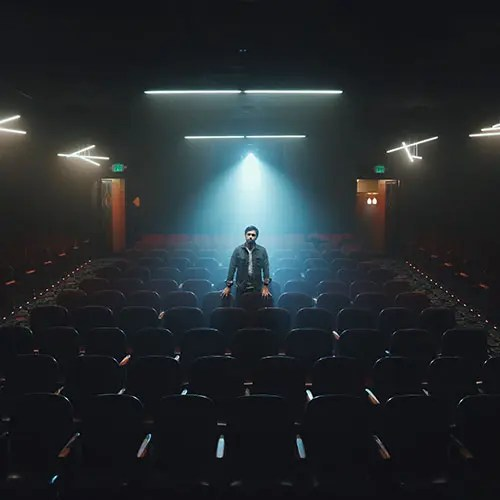 man standing in empty movie theater