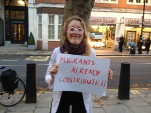 Docs Not Cops at the International Students Demonstration - person holding a sign that says 'Migrants already contribute'