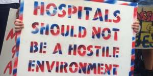 """Hospitals Should not be a Hostile Environment"" spray painted placard"