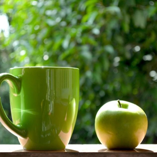 green mug and apple