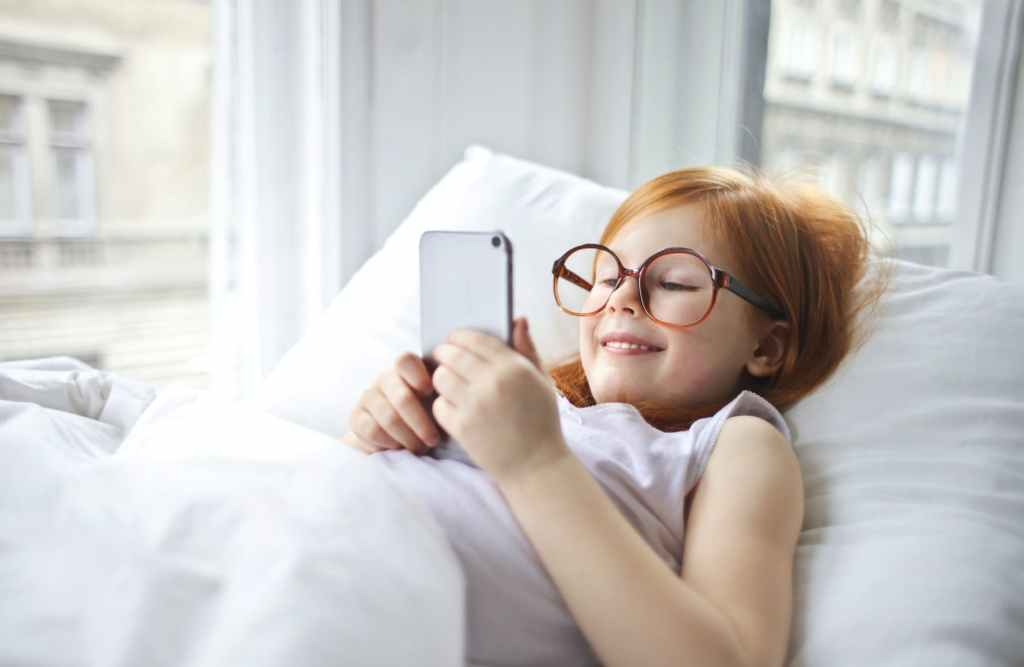 photo of smiling young girl in white tank top lying on bed while using a smartphone