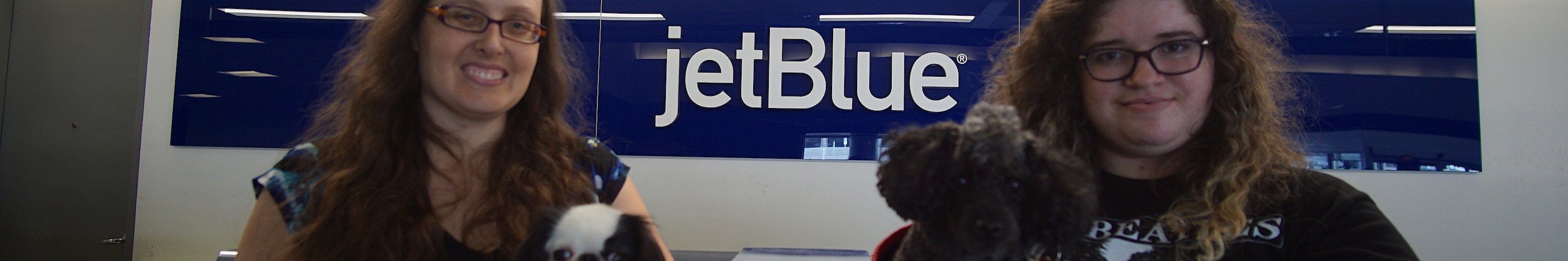 Veronica holding Hestia, and Scarlet holding Gigi in front of a JetBlue sign