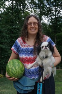 Veronica and Hestia with a nice green watermelon.  Veronica's shirt is red, white, and blue, and she has on a jeans skirt.  Hestia has her regular leash and collar on.