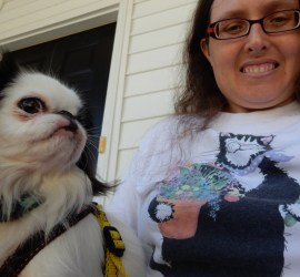 """Veronica wearing a """"Hairy Potter"""" shirt with a furry cat and a potted plant. Hestia looks on."""