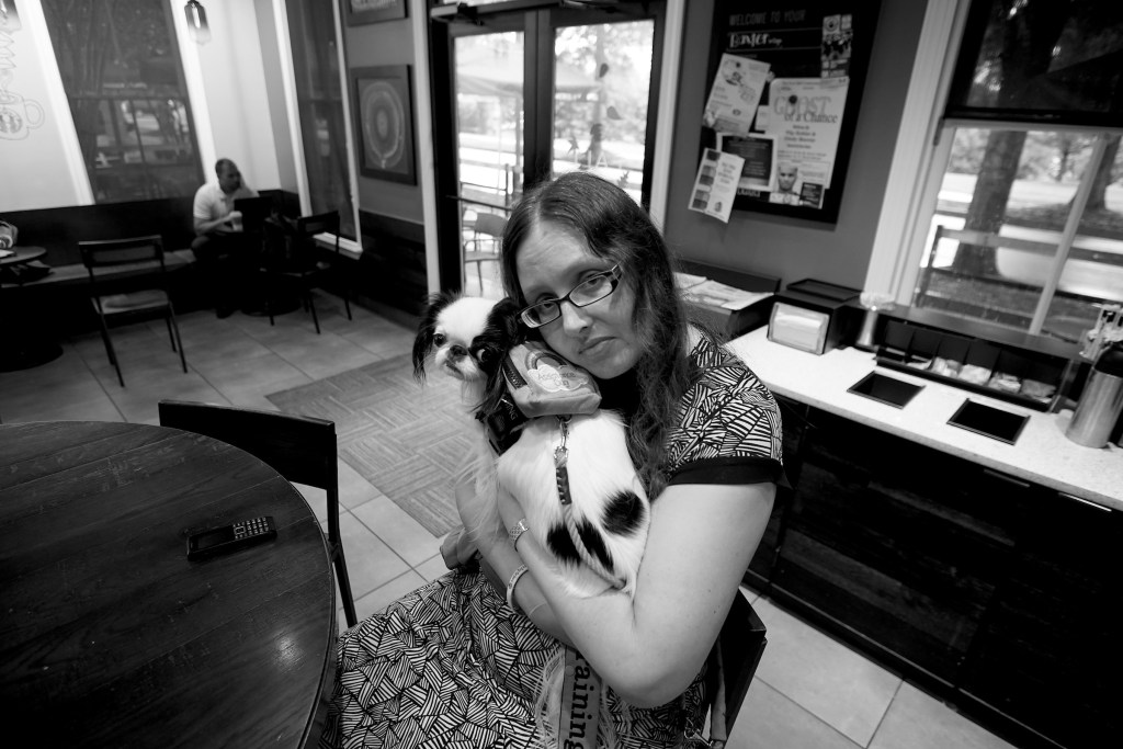 Black and white photo of Veronica with Hestia on her chest. Veronica is leaning into Hestia, who is leaning into her for deep pressure therapy.