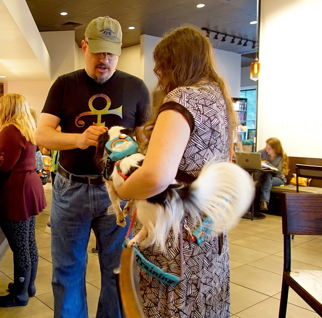 Veronica holding Hestia and CJ saying hello to Hestia. Hestia's long tail is swishing because she loves CJ!