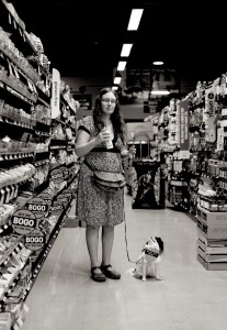 Black and white photo of Veronica looking anxious and Hestia looking up at her in the aisle of the grocery store.