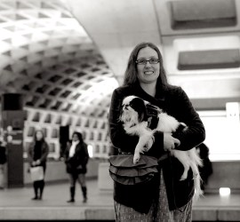 Veronica holding Hestia in the Metro. The picture is in black and white, which sets off the recessed rectangles of the walls and ceiling nicely.