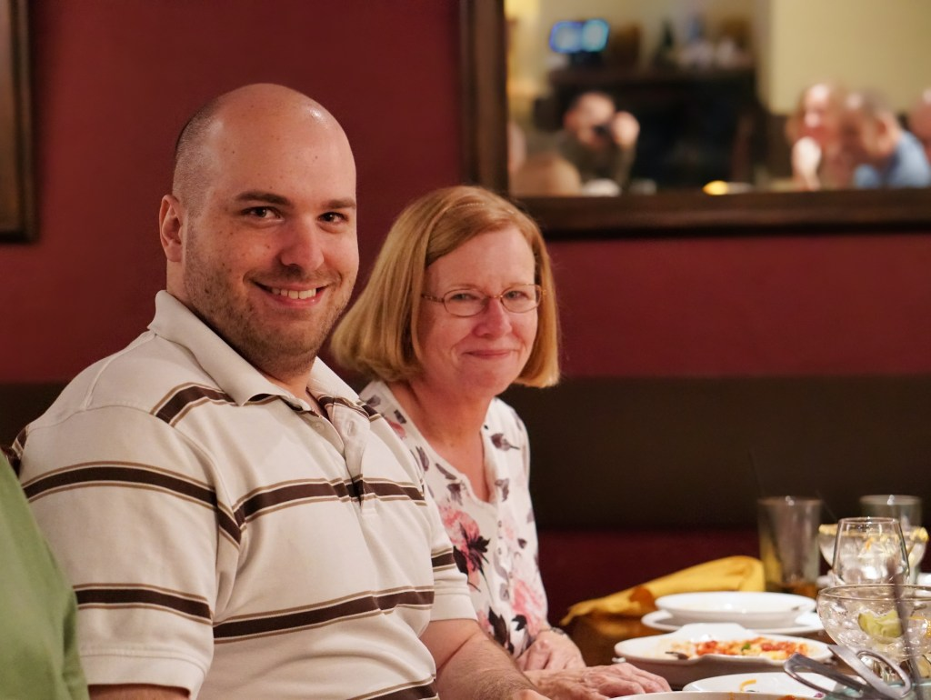 Tony and his mom, Suzanne.  Tony is wearing a striped shirt, and Suzanne has a floral shirt on.