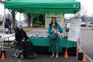 Brad and Veronica in front of a  table with black and green tablecloths, filled with PSDP materials.  There is a PSDP banner with our mission statement on it behind us, and a green canopy overhead.