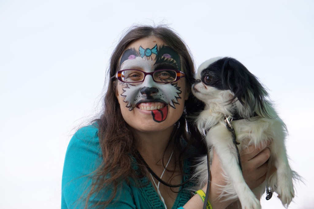 Closeup of Veronica's fresh face painting with Hestia sniffing Veronica's face trying to determine who this giant dog is!
