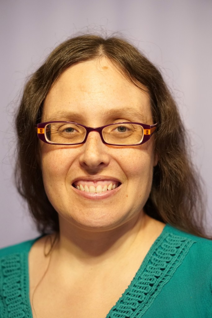 Woman with purple and orange glasses and long brown hair smiling. This is Veronica wearing her hair normally and you can't see the hearing aids.