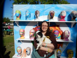 A small black and white dog being carried by a girl in a brown shirt, turquoise skirt, with long brown hair. They are in front of a display of decoupaged heads to encourage people to think about mental illness and express their feelings about it.