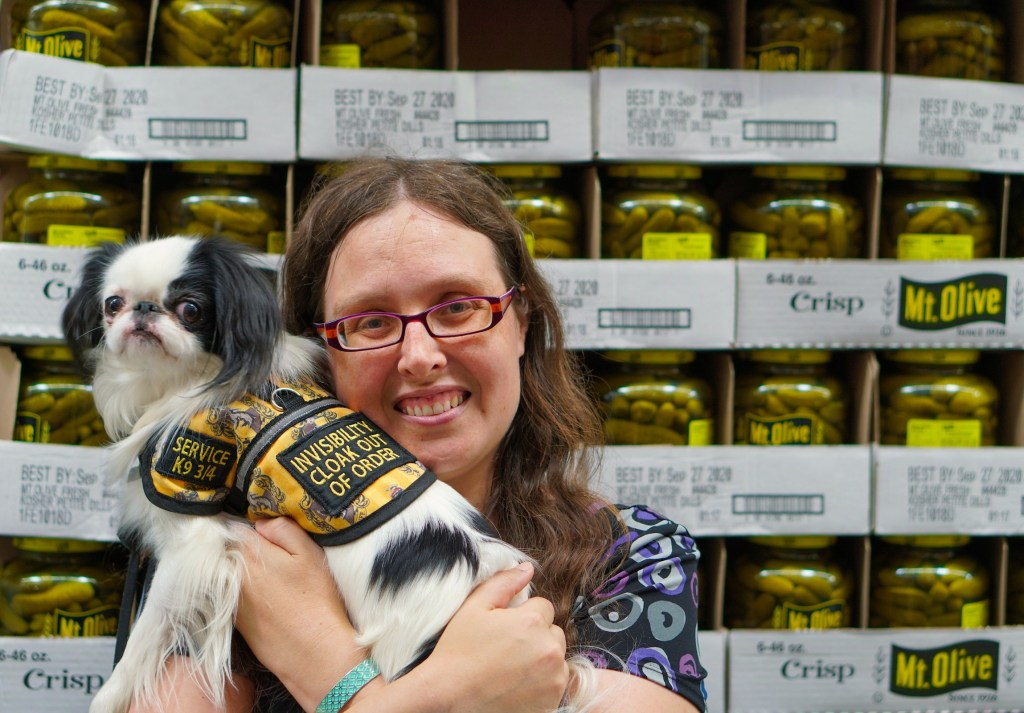 Veronica holding Hestia up next to her face in front of the pickles.  Hestia is wearing her Hufflepuff vest with the invisibility cloak patch and the service k9 3/4 patch showing.