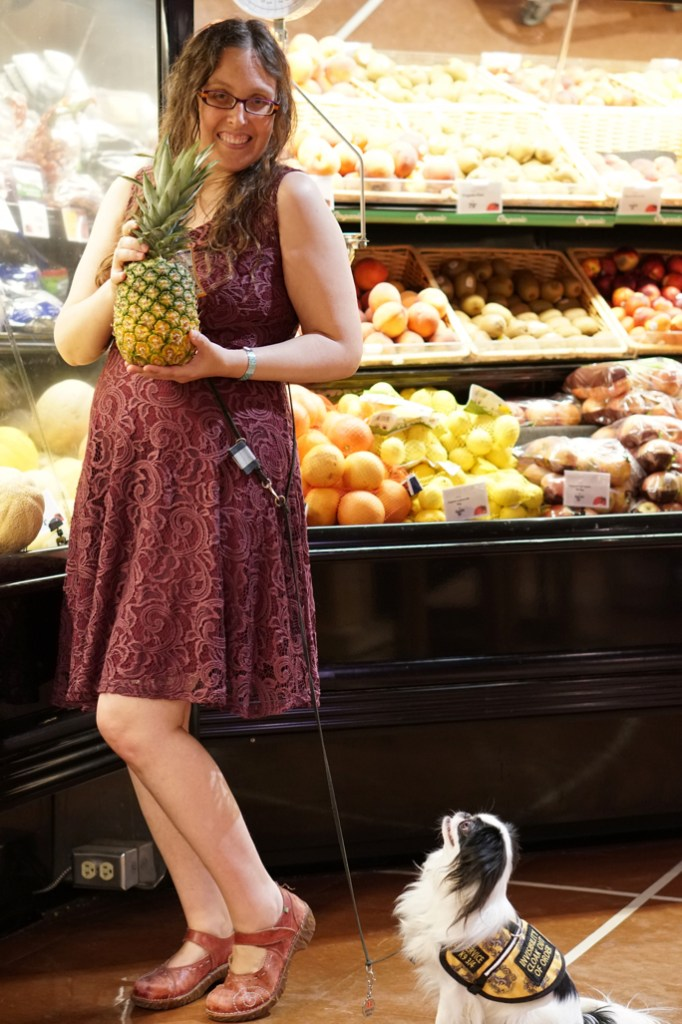 Veronica turned to the side with knees bent, holding a pineapple.  Hestia is looking up expectantly.